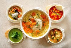 Different bowls with meat, poultry, vegetable and legume soups. stock image