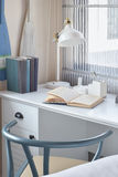White table with wooden chair books and lamp in modern working area Stock Photo