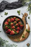 Flat lay, strawberries on black plate, wooden cutting board stock photography