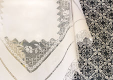 A white tablecloth with a lace pattern and an embroidered blanke Stock Image