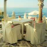 White tables and chairs in greek cafe by the sea coast, Crete, G Stock Photos
