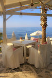 White tables and chairs on sea coast, Crete, Greece. Royalty Free Stock Images