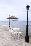 White tables and chairs on sea pier, Greece. Stock Images