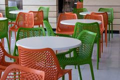 White tables, orange and green chairs in cafe in the food court of shopping center airport or train station. The room is without royalty free stock images