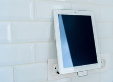 White tablet is charging Royalty Free Stock Photos