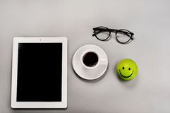 White tablet computer with a cup of coffee. And glasses on a gray surface. Top view Stock Photography