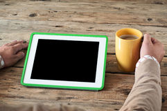 White tablet computer  with a cup of coffee. On a wooden table. Male works with help of the tablet. Top view Stock Image