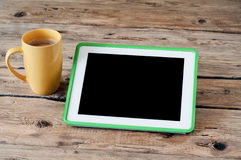 White tablet computer  with a cup of coffee. On a wooden table. Male works with help of the tablet. Top view Royalty Free Stock Photo