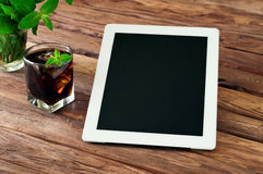 White tablet computer with a glass glass of cola with ice and mi stock photo