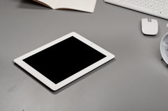 White tablet computer on a grey table Stock Photo