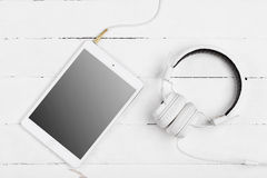 White tablet computer and music headphones Stock Images
