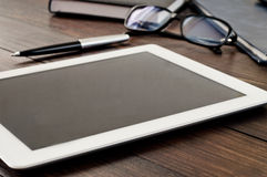 White tablet computer on office wooden table closeup Royalty Free Stock Image
