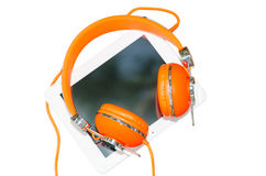 White tablet computer with orange headphones isolated on white Stock Photography