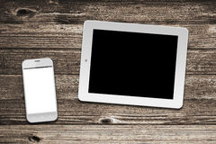 White tablet computer and smart phone with isolated screens Royalty Free Stock Image