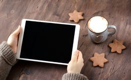 White tablet in hand. Wooden table, fragrant cocoa and cookies royalty free stock photos