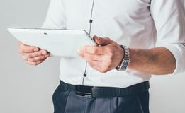 A white tablet is in the hands of a man. He stands in a white shirt and black trousers and reads information from the gadget stock photography