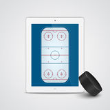White tablet with ice hockey puck and field on the screen. Stock Photography