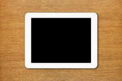 White Tablet PC with black screen on the table Royalty Free Stock Photo