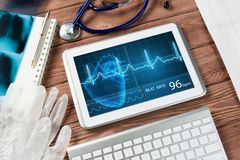 Digital technologies in medicine. White tablet pc and doctor tools on wooden table stock photography