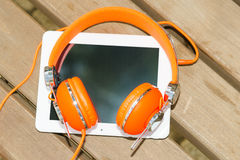 White tablet PC with orange headphones on the wood bench Royalty Free Stock Images