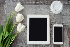 White tablet, phone, coffee and flowers are on the table. Work at home. Freelance.  stock photos