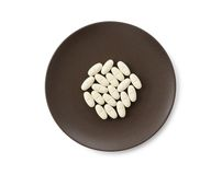 White tablet pills in plate Royalty Free Stock Photo