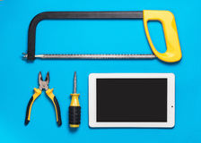 White Tablet and set of yellow construction tools to repair on a blue table: saw, screwdriver, pliers. Top view Stock Photo