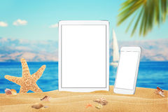 White tablet and smart phone with isolated white screen for mockup. Summer on beach, sea, sand, blue sky, palm, starfish and shell Royalty Free Stock Image