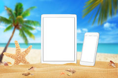 White tablet and smart phone with isolated white screen for mockup. Summer on beach, sea, sand, blue sky, palm, starfish and shell Stock Image