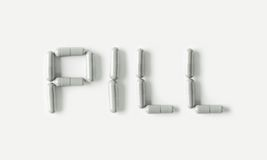 White tablets capsules in shape of word Pill. Health Life concept isolated. Royalty Free Stock Photography