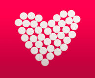 White tablets into a heart. An arrangemet of little white tablets into a heart, on white Royalty Free Stock Photos