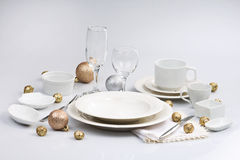 White tableware. Laying tea cup, coffee cup, plate, bowl, Christmas balls knife, fork, cutlery stemware Stock Image
