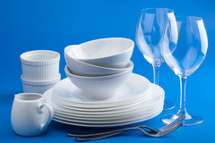 White tableware over blue background. Various white tableware over blue background Stock Photo