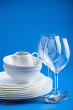 White tableware over blue background Royalty Free Stock Photography