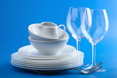 White tableware over blue background Royalty Free Stock Photos
