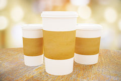 White take out coffee cups. Disposable white paper coffee cups with blank brown labels on wooden table. Modern city background. Mock up, 3D Rendering Royalty Free Stock Photo