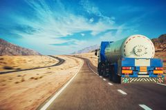 White tanker and trucks driving along picturesque desert mountain highway. royalty free stock photo