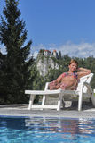 White tanned woman sunbathing. Bled Castle in background. Stock Photo