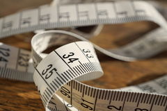White tape measure tape measuring length in meters and centimeters on the woodensurface as symbol of tool used by tailor Royalty Free Stock Image