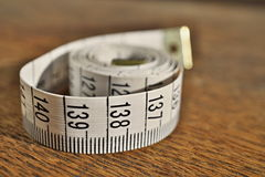 White tape measure tape measuring length in meters and centimeters on the woodensurface as symbol of tool used by tailor Royalty Free Stock Photo