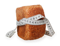 White tape measure wrapped around whole wheat bread Stock Image