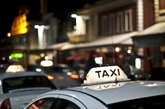 White taxi. Focus on a Taxi sign in a street night scene Stock Photos