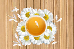 White tea cup on chamomile flowers on wooden texture close-up ba Royalty Free Stock Image