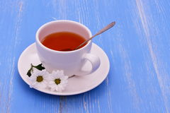 White tea cup and flowers on blue wooden horizontal Royalty Free Stock Photography