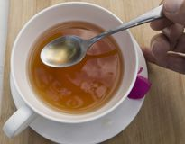White Tea cup with herbal tea and a silver spoon royalty free stock photo