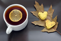 White tea cup with lemon on a saucer with cookies and autumn lea Stock Image