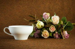 White tea cup beside by roses Stock Photo