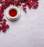 White tea cup on a saucer Bunches of berries Viburnum on rustic wooden background top view space for text Stock Photos
