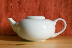 White tea-kettle. On the wooden floor royalty free stock photo