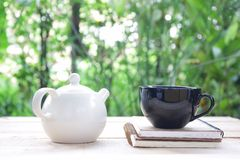 White tea kettle with cup and notebooks Royalty Free Stock Images